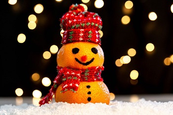 tangerine-snowman-in-the-snow-on-a-blurry-background-of-luminous-garlands.jpeg